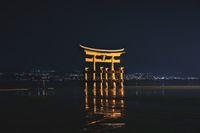 The floating Torii Gate of Itsukushima Shrine Illuminated in the night in front of city lights in Miyajima, Hiroshima, Japan