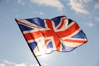 UK Great Britain flag waving in cloudy blue sky