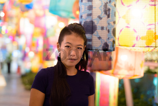 Portrait of beautiful Asian woman with traditional colorful lantern lights outdoors at night