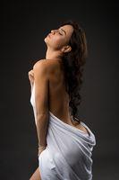 Alluring woman in white cloth in studio