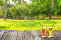 Green field with 2 cocktail glasses on table