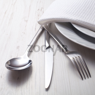 fork, knife, spoon and a white plate