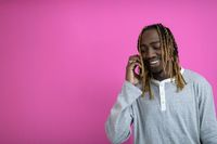 afro guy uses a phone while posing in front of a pink background.