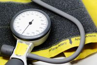 a portable sphygmomanometer resting on a yellow cuff for adults with a velcro closure.