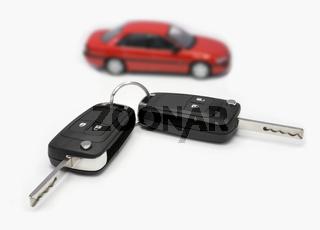 Zündschlüssel mit Auto im Hintergrund