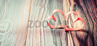 Two paper hearts on wooden background in vintage look - soft focus. Symbol of love. Space for text.