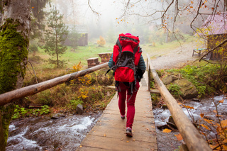 Woman is going across the wooden bridge while hiking