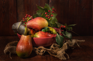 ripe pears and other fruits on a dark wooden background in a rustic style