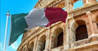 The Italian flag flapping in the wind with the Colosseum blurred in the background