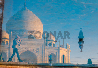 Taj Mahal and a photographer reflected in the garden's pool