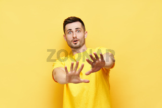 Young displeased man making stop gesture sign say no