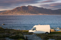 Camper van motorhome with solar panels view on a sea landscape with mountains living van life in Galiza, Spain