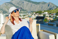 beautiful woman in straw hat enjoying evening with wine glass at resort. Luxury hotel terrace.