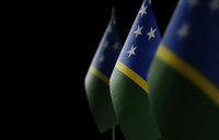 Small national flags of the Solomon Islands on a black background