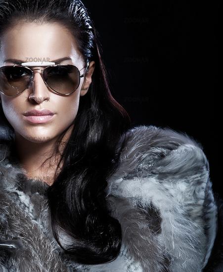 Portrait of brunette woman wearing sunglasses and beautiful fur