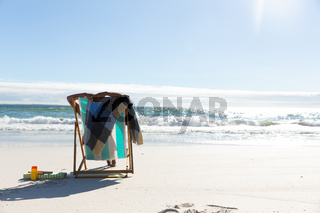 Mixed race woman on beach holiday sitting in deck chair relaxing