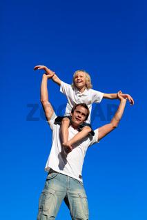 Man giving young boy piggyback ride smiling