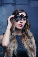 Young blonde woman in black lace mask and black dress. Female on smoke and metal wall background.