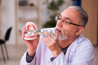 Old male dentist teacher sitting in the classroom