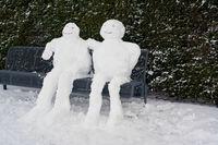 Schneemann und Schneefrau auf einer Parkbank im Winter