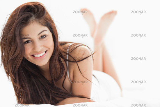 Woman lying down with her legs crossed and raised, smiling with her arms on the bed