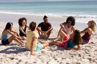 Multi-ethnic group of male and female sitting on the beach