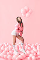Full length portrait of young trendy woman posing with pink balloons on pink background