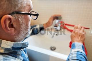 Installateur repariert defekten Wasserhahn im Badezimmer