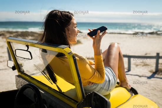 Caucasian woman lying on a beach buggy by the sea talking on smartphone