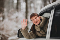 Happy woman driving car in winter