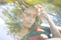 Motion blured image of happy young woman driving a car on a summer road trip travel vacations. Shot trough windshield.