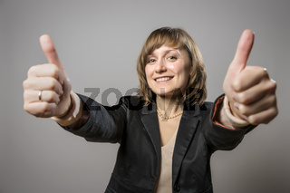 Young business woman with two thumbs held high