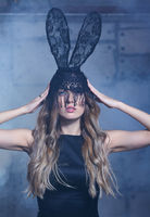 Young blonde woman in black rabbit or hare fancy mask and black dress. Female on smoke and metal wall background.