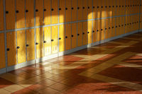 Sun shines on empty elementary school hall, numbered lockers at the wall
