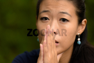 Close-up portrait of beautiful rebel Asian woman face looking stressed outdoors