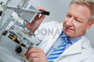 Optiker bohrt in Werkstatt