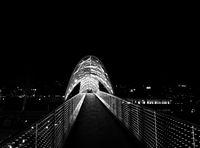 Bridge of Peace over Kura River with illuminated at night. Tbilisi, Georgia.