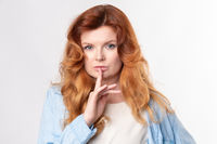 Portrait of young business woman keeping finger on her lips and asking to keep quiet, isolated over white background