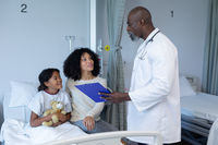 African american male doctor talking to mixed race mother and her sick daughter, in hospital bed