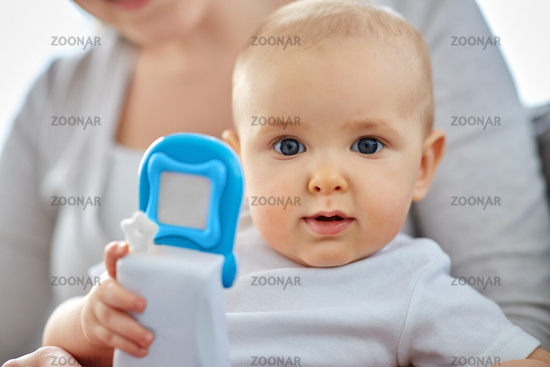 mother with baby playing with toy phone at home