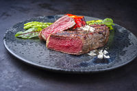 Modern style barbecue dry aged wagyu roast beef steak with green asparagus and lettuce served as close-up on a Nordic design plate