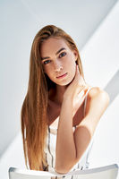 Close up portrait of pretty young woman looking to camera with sun lights on background