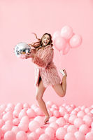 Full length portrait of joyful pretty woman jumping with party disco ball