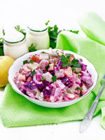 Salad with herring and beetroot in bowl on napkin