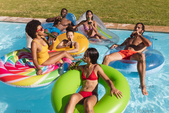 Diverse group of friends having fun playing on inflatables in swimming pool