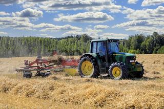 John Deere Tractor and Rake Working in Field
