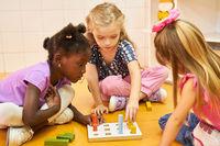 Multikulturelle Kinder spielen Steckspiel mit Bausteinen