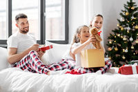happy family with christmas gifts in bed at home