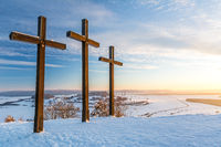 Summit crosses on a mountain peak in a beautiful winter landscape in the Swabian Alps at sunset