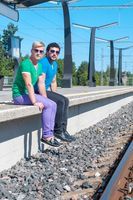 Shot of two young men sitting on platform